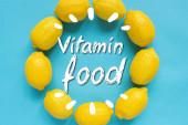 horní pohled na zralé žluté citrony uspořádané v kulatém rámečku s vitaminovou potravinovou ilustrací na modrém pozadí