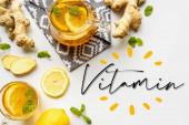 vrchní pohled na horký čaj na ubrousku v blízkosti zázvoru kořen, citron a máta na bílém pozadí, vitamin ilustrace