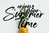 top view of ripe pineapple with green leaves on white background with enjoy your summertime illustration
