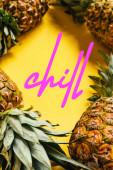 selektivní zaměření čerstvých zralých ananasů se zelenými listy na žlutém pozadí s chladnou ilustrací