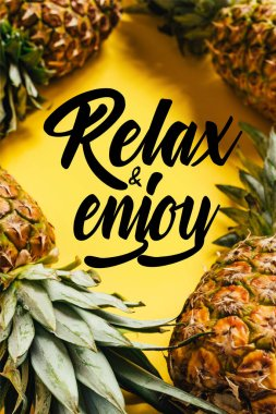 Selective focus of fresh ripe pineapples with green leaves on yellow background with relax and enjoy illustration stock vector
