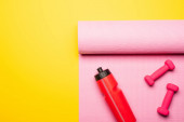top view of red sports bottle, pink fitness mat and dumbbells on yellow background