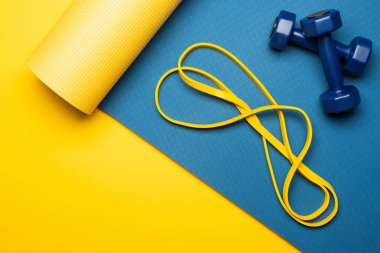 top view of blue fitness mat with dumbbells and resistance band on yellow background