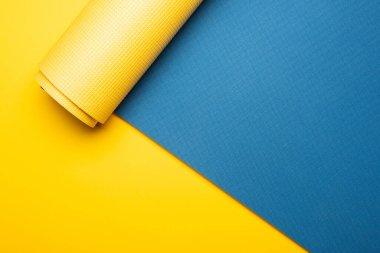 top view of blue fitness mat on yellow background