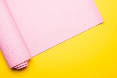 top view of pink fitness mat on yellow background
