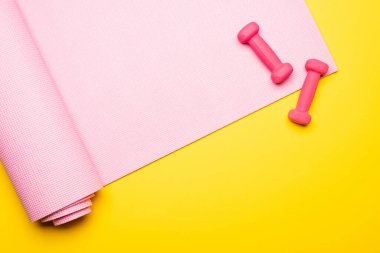 top view of pink fitness mat and dumbbells on yellow background