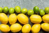 pohled shora na zralé žluté citrony a zelené limetky na betonovém povrchu