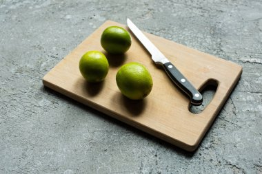 Ripe limes on wooden cutting board with knife on concrete textured surface stock vector