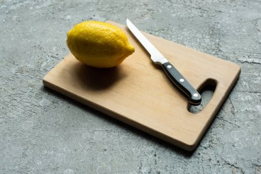 Ripe yellow whole lemon on wooden cutting board with knife on concrete textured surface stock vector