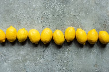 Top view of ripe yellow lemons in row on concrete textured surface stock vector