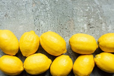 Top view of ripe yellow lemons on concrete textured surface stock vector