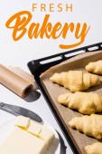 selektivní zaměření syrových croissantů na tác na pečení, máslo, nůž v blízkosti čerstvého pekařského nápisu na bílém