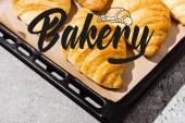 pečené a lahodné croissanty na tácu na pečení v blízkosti pekařského nápisu na betonovém šedém povrchu