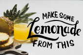fresh pineapple juice near sliced fruit on wooden cutting board near make some lemonade from this lettering on white