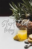fresh pineapple juice near delicious fruit on wooden cutting board and start diet today lettering on white and black