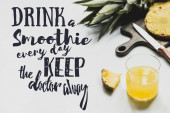 pineapples on cutting board near glass of orange juice and drink a smoothie every day keep the doctor away lettering on white
