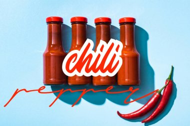 Top view of chill pepper lettering near tomato sauce in bottles on blue background stock vector