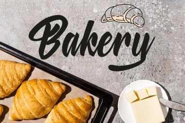 Top view of baked croissants on baking tray near butter, knife and bakery lettering on concrete grey surface stock vector