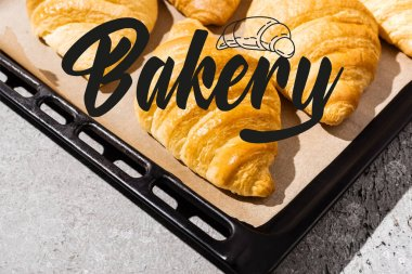 Baked and delicious croissants on baking tray near bakery lettering on concrete grey surface stock vector