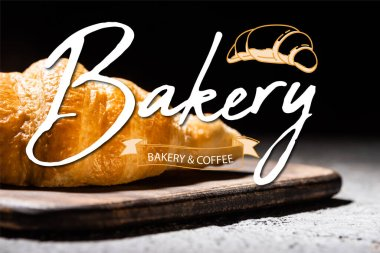 Close up of baked croissant on wooden cutting board near bakery and coffee lettering on black stock vector