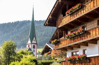 The Saint Oswald Parish Church and a typical wooden balcony with flowers in Alpbach, a town in western Austria in the state of Tyrol