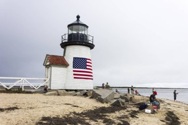 Nantucket, Massachusetts. Brant Point Light, a lighthouse located on the harbor of Nantucket Island, with several people fishing and an American flag