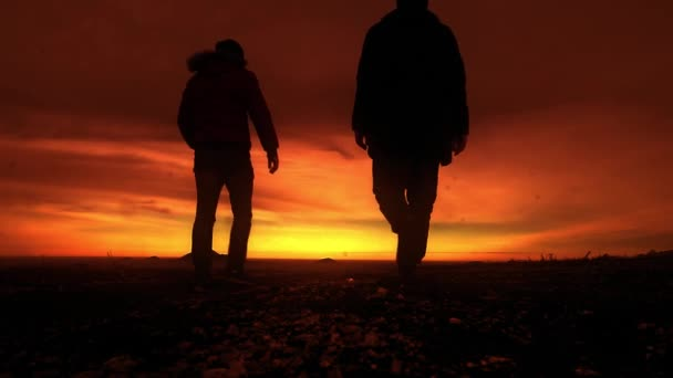 two men join hands and go into the sunset. lgbt