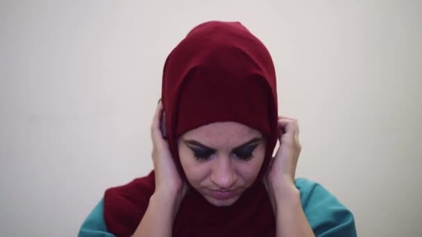 muslim woman straightens clothes and looks into the camera