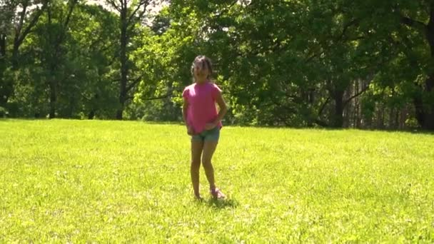 little asian girl dancing in the park on the meadow, day