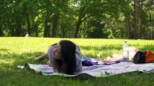 mladá asijská dívka leží na mýtině v parku, den