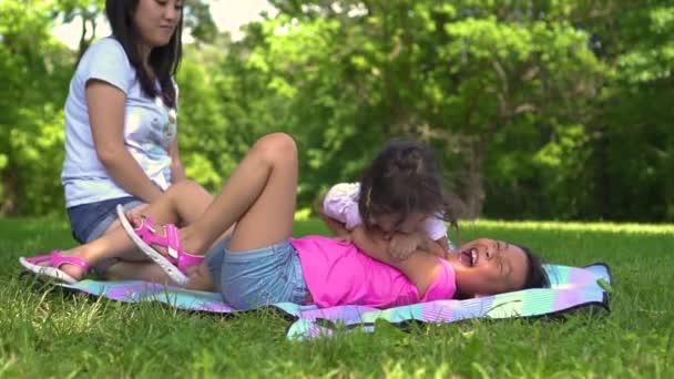 malá Asijská děvčata na louce v parku, den