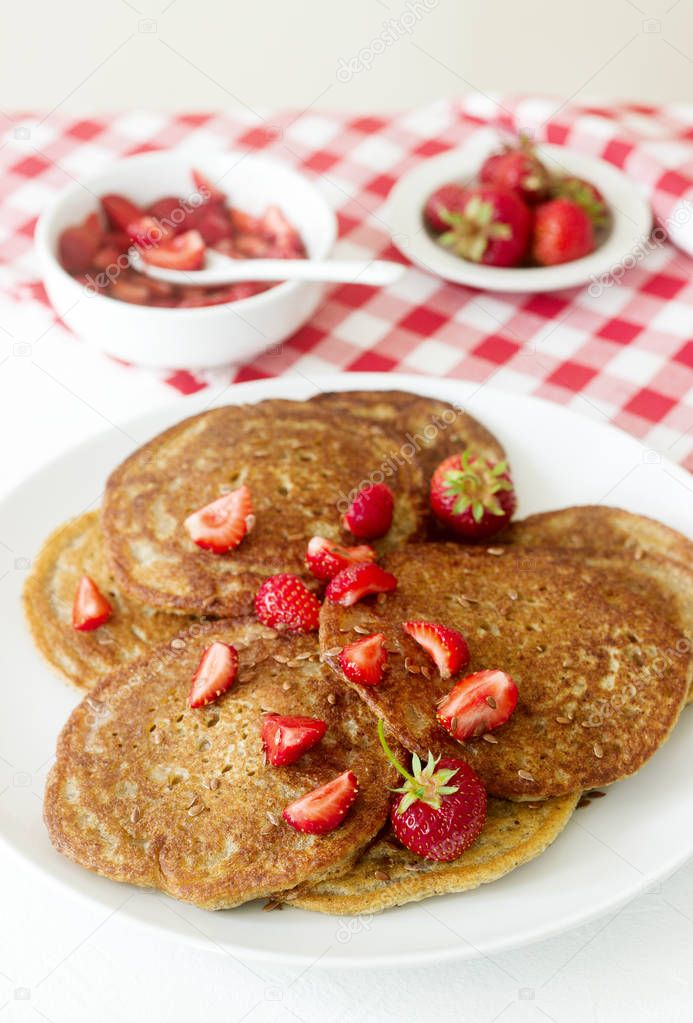 Useful breakfast of pancakes with linseed flour and strawberry-honey sauce.