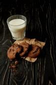 Fotografia vista del primo piano dei biscotti al cioccolato su carta sgualcita e vetro di latte su superficie di legno nero