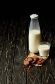 Detailní pohled čokoládové sušenky, mléko v láhvi a sklo na dřevěné pozadí