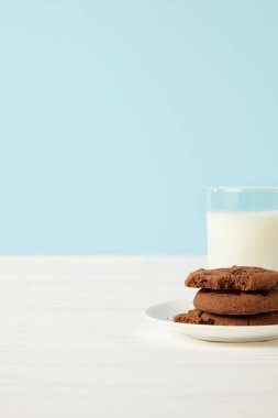 chocolate cookies on saucer and milk glass on blue background