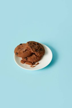 closeup view of chocolate cookies in saucer on blue background