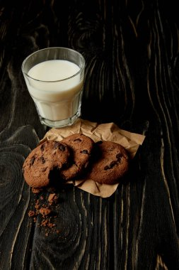 closeup view of chocolate cookies on crumpled paper and milk glass on black wooden surface