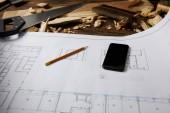 Fotografie Detailní pohled smartphone a tužka na modrotisk, pilkou a štětec s dřevěnými figurkami na stole