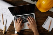 oříznutý obraz architekta psaní na notebooku u stolu s dlátem, vodováha, ochranné helmy, blueprint, učebnice a tužky