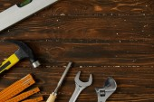 collapsible meter, hammer, adjustable wrench, spanner, chisel and spirit level on wooden surface