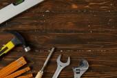 skládací metr, kladivo, nastavitelný klíč, klíč, dláto a vodováha na dřevěný povrch