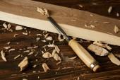 zblízka pohled na dřevěné prkno a kousky s dlátem na hnědý stůl