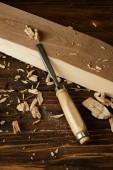 zblízka pohled dlátem a dřevěné kusy hnědé tabulky