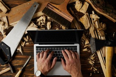 cropped image of carpenter typing on laptop surrounded by different tools on table