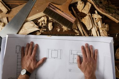 cropped shot of architect hands on blueprint at table with paintbrush, handsaw and wooden chips on table