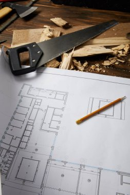 closeup view of architectural blueprint, pencil, handsaw, axe and coping saw on wooden table