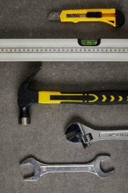 spirit level, hammer, adjustable wrench ans spanner on gray surface