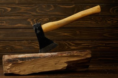 closeup view of sticking axe in log on brown wooden surface