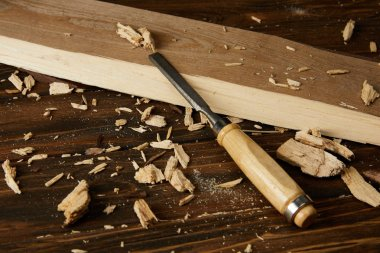 close up view of wooden plank and pieces with chisel on brown table