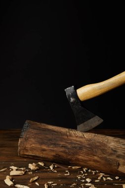 close up view of sticking axe in log and wooden chips on black background